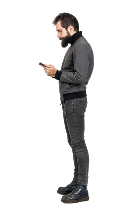 Side view of stylish bearded hipster typing on his smartphone. Full body length portrait isolated over white studio background.